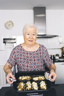 Portrait of senior woman showing prepared food in the kitchen - GEMF01114