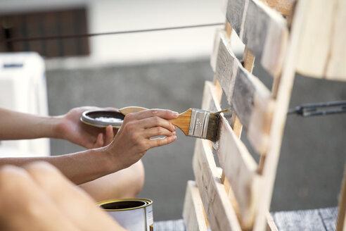 Close-up of woman applying glaze on pallet - KNTF00539