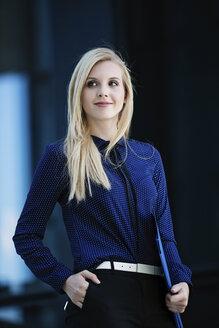 Portrait of smiling blond businesswoman with folder - GDF01130
