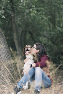 Woman sitting on forest ground kissing her dog - SKCF00216