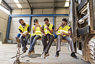 Workers having lunch on the shovel of a giant forklift - JASF01173