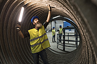 Worker examining giant construction tube - JASF01182