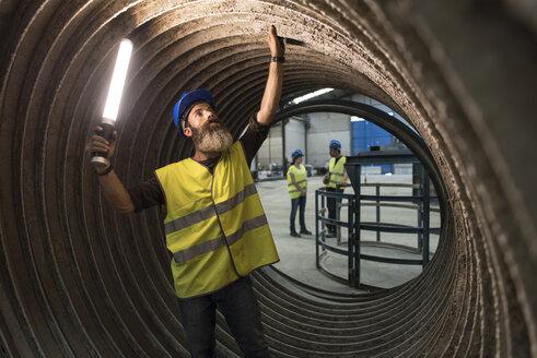Worker examining giant construction tube - JASF01182