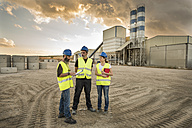 Three people in safety vests on industrial site - JASF01197