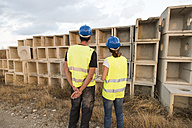 Man and woman in safety vestslooking at  concrete structures - JASF01203