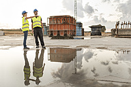Man and woman in safety vests on industrial site - JASF01209