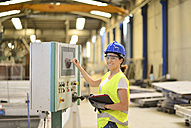 Smiling woman operating control in factory - JASF01218