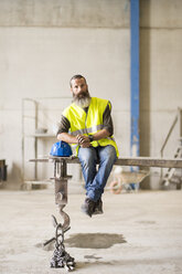 Bearded worker sitting on forklit shovel - JASF01221