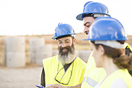 Three people in safety vests on industrial site - JASF01233