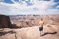 USA, Utah, Young man standing on Dead Horse Point looking to Colorado River - EPF00155