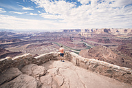 USA, Utah, Young man standing on Dead Horse Point looking to Colorado River - EPF00158
