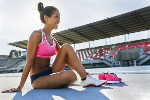 Athlete in stadium changing shoes - MGOF02473