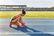 Female athlete tying shoes on race track - MGOF02485