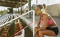 Female athlete taking a break, listening to music - MGOF02491