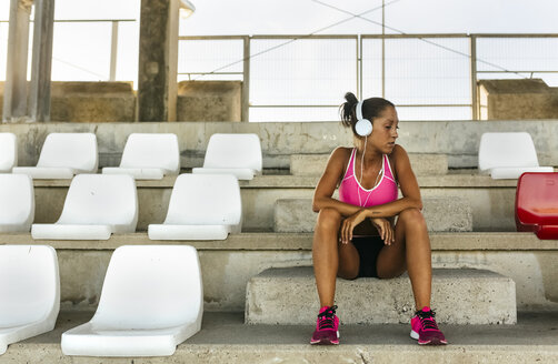 Female athlete taking a break, listening to music - MGOF02494