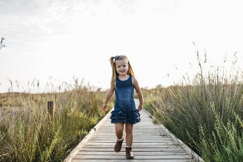 Smiling little girl walking on boardwalk in nature - JRFF00865