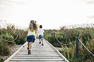Back view of two little children playing together on boardwalk in nature - JRFF00871