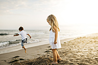 Little boy and girl playing on the beach - JRFF00883