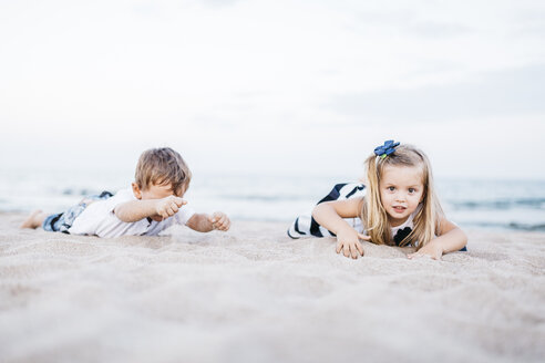 Little boy and little girl playing on the beach - JRFF00898