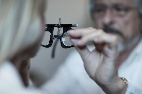 Optometrist adjusting test frame for patient - ZEF10566