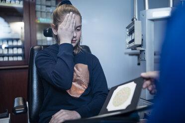 Girl covering eye for eye test - ZEF10593