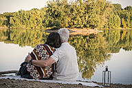 Relaxed senior couple at a lake in the evening - ONF01037