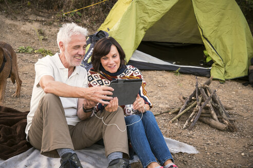Happy senior couple with tablet at a tent - ONF01043