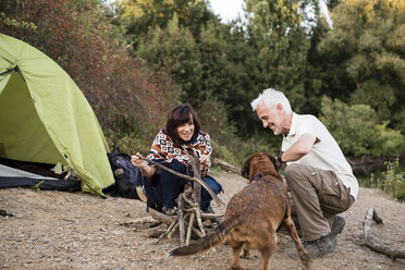 Senior couple with dog at a tent preparing a campfire - ONF01046