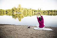 Senior woman stretching at a lake - ONF01070