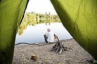 Senior man with dog camping at a lake - ONF01076