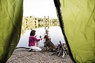 Senior couple camping with dog at a lake - ONF01079