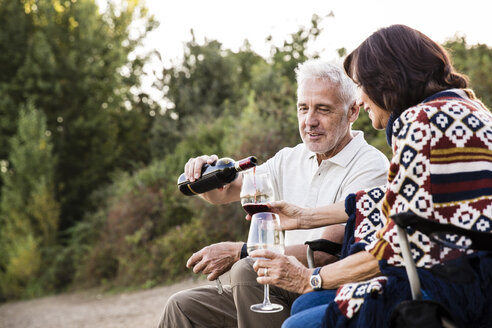 Senior man pouring red wine into glass for his wife - ONF01082