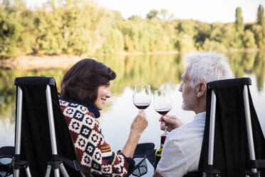 Senior couple clinking wine glasses at a lake in the evening - ONF01085