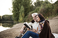 Happy senior couple with wine and book at a lake - ONF01088