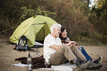 Happy senior couple with cell phone at a tent - ONF01091