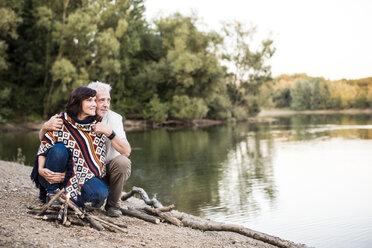 Senior couple at campfire at a lake - ONF01094