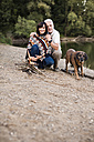 Senior couple with dog at campfire at a lake - ONF01097