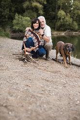 Senior couple with dog at campfire at a lake - ONF01097