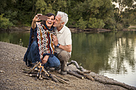 Happy senior couple at a lake taking a selfie at campfire - ONF01100