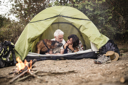 Senior couple with dog lying in tent at campfire - ONF01103