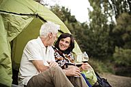 Senior couple sitting with wine in a tent - ONF01106
