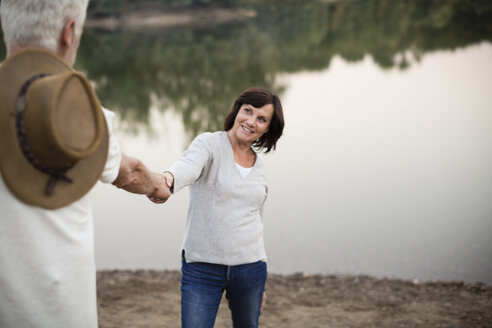 Happy senior couple hand in hand at a lake - ONF01112