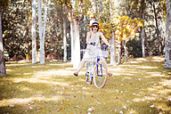 Woman balancing on bicycle in autumnal park - JPSF00017