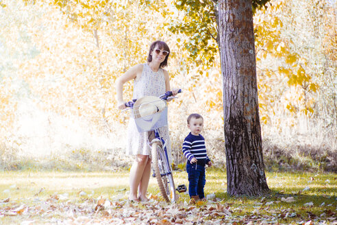 Mother with bicycle and her little son in autumnal park - JPSF00020