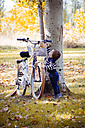 Toddler taking autumn leaf from bike - JPSF00023