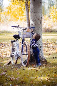 Toddler taking autumn leaf from bike - JPSF00023