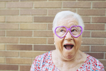 Portrait of senior woman wearing heart-shaped glasses pulling funny faces - GEMF01120