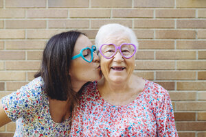 Happy granddaughter and grandmother wearing heart-shaped glasses - GEMF01123