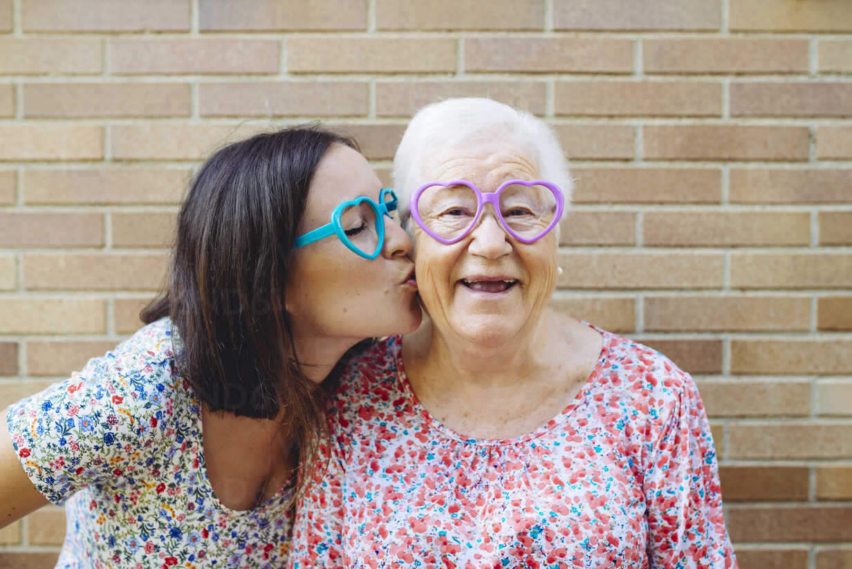 Happy granddaughter and grandmother wearing heart-shaped glasses - GEMF01123 - Gemma Ferrando/Westend61