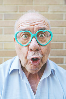 Portrait of senior man wearing heart-shaped glasses pulling funny faces - GEMF01126